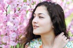 Портрет молодой красивой девушки на пинке цветет предпосылка, поднимающее вверх стороны близкое Стоковое Изображение RF