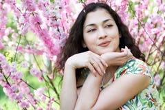 Портрет молодой красивой девушки на пинке цветет предпосылка, поднимающее вверх стороны близкое Стоковое фото RF