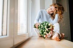 Портрет молодой красивой девушки с букетом роз около окна стоковое изображение