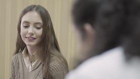 Портрет молодой красивой девушки с длинными волосами в консультации с доктором в шкафе сток-видео
