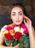 Портрет молодой красивой женщины, брюнет с букетом роз Она лежит на поле и держит ее руку стороной стоковые фотографии rf