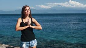 Портрет молодой красивой женщины делает тренировку йоги, океан на предпосылке сток-видео