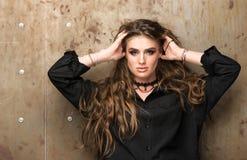 Портрет молодой красивой женщины около стены Модель бежит ее руки через ее волосы Стоковая Фотография RF