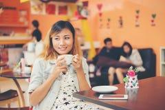 Портрет молодой красивой женщины сидя в кафе держа горячим Стоковая Фотография