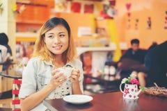 Портрет молодой красивой женщины сидя в кафе держа горячим Стоковое Изображение RF