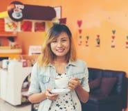 Портрет молодой красивой женщины сидя в кафе держа горячим Стоковые Фото