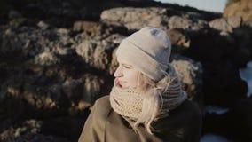 Портрет молодой красивой женщины стоя около горы и смотря вокруг, волосы развевая на ветре в солнечном дне видеоматериал