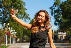 Портрет молодой красивой женщины smiley делая selfie outdoors Стоковые Изображения