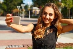 Портрет молодой красивой женщины smiley делая selfie outdoors Стоковое фото RF