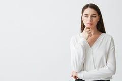Портрет молодой красивой коммерсантки брюнет мечтая думая хмуриться над белой предпосылкой Рука на подбородке Стоковое Фото