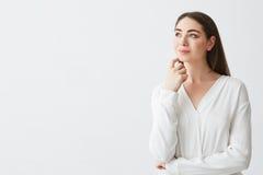 Портрет молодой красивой коммерсантки брюнет мечтая думая хмуриться над белой предпосылкой Рука на подбородке Стоковое Изображение RF