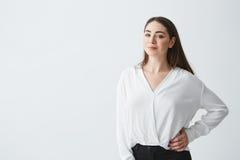 Портрет молодой красивой коммерсантки брюнет усмехаясь смотрящ камеру представляя над белой предпосылкой Стоковая Фотография RF