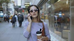 Портрет молодой красивой коммерсантки в солнечных очках говоря на мобильном телефоне и выпивая кофе внутри к центру города видеоматериал