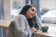 портрет молодой красивой милой девушки брюнет в кофе серого свитера выпивая Стоковые Фото