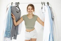 Портрет молодой красивой счастливой девушки смотря вне наблюдать шкафа вешалок усмехаясь на камере над белой стеной Стоковые Изображения RF