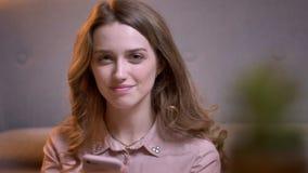 Портрет молодой курчавой девушки наблюдая в turnes смартфона к камере и улыбки мило в уютном доме акции видеоматериалы