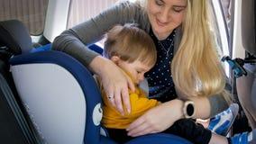 Портрет молодой матери регулируя ремни безопасности безопасности детей автомобиля Стоковое Фото