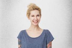 Портрет молодой милой девушки с белокурыми волосами, прокалыванным носом и усмехаться и wink футболки татуировок, носить вскользь Стоковое Фото