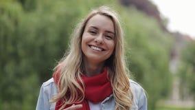 Портрет молодой милой женщины смеясь счастливым наслаждаясь положительным образом жизни нося красное положение шарфа в парке r сток-видео