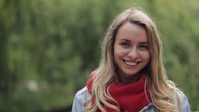 Портрет молодой милой женщины смеясь счастливым наслаждаясь положительным образом жизни нося красное положение шарфа в парке видеоматериал