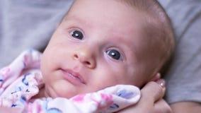 Портрет молодой милой newborn дочери лежит на руках и дозорах матери s joyfully и мило в живущей комнате видеоматериал