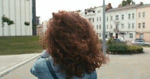 Портрет молодой очаровательной девушки с вьющиеся волосы и расчалок на зубах счастливо идя вдоль улицы акции видеоматериалы
