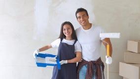 Портрет молодой пары в новом доме красящ и украшающ стену их дома сток-видео