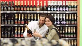 Портрет молодой пары моды в винном магазине Выбор вина для обедающего акции видеоматериалы