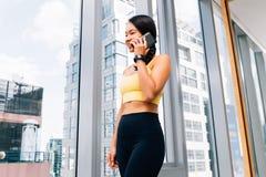Портрет молодой подходящей женщины говоря на хоне на высоком спортзале подъема Женское изображение модели фитнеса стоковые фотографии rf
