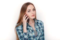 Портрет молодой прелестной белокурой женщины в голубой рубашке шотландки наслаждаясь имеющ эмоциональный переговор на smartphone стоковые изображения