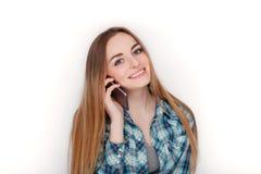 Портрет молодой прелестной белокурой женщины в голубой рубашке шотландки наслаждаясь имеющ эмоциональный переговор на smartphone стоковое изображение rf