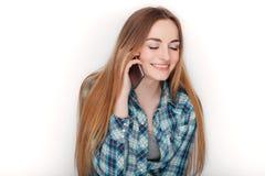 Портрет молодой прелестной белокурой женщины в голубой рубашке шотландки наслаждаясь имеющ эмоциональный переговор на smartphone стоковые изображения rf