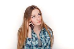 Портрет молодой прелестной белокурой женщины в голубой рубашке шотландки наслаждаясь имеющ эмоциональный переговор на smartphone стоковое фото rf