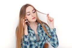 Портрет молодой прелестной белокурой женщины в голубой рубашке шотландки наслаждаясь имеющ эмоциональный переговор на smartphone стоковая фотография rf