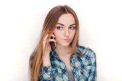Портрет молодой прелестной белокурой женщины в голубой рубашке шотландки наслаждаясь имеющ эмоциональный переговор на smartphone стоковые фото