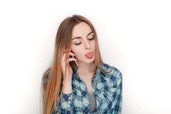 Портрет молодой прелестной белокурой женщины в голубой рубашке шотландки наслаждаясь имеющ эмоциональный переговор на smartphone стоковое фото