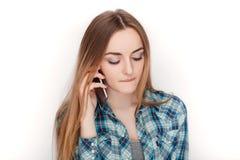 Портрет молодой прелестной белокурой женщины в голубой рубашке шотландки наслаждаясь имеющ эмоциональный переговор на smartphone стоковое изображение