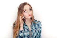 Портрет молодой прелестной белокурой женщины в голубой рубашке шотландки наслаждаясь имеющ эмоциональный переговор на smartphone стоковая фотография