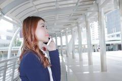 Портрет молодой привлекательной азиатской бизнес-леди говоря на телефоне для его работы на тротуаре предпосылки города Стоковое Изображение