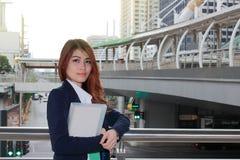Портрет молодой привлекательной азиатской бизнес-леди стоя и держа связыватель кольца на городской предпосылке города Стоковые Изображения