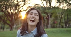 Портрет молодой привлекательной азиатской женщины усмехается счастливо в камеру в парке лета на заходе солнца акции видеоматериалы
