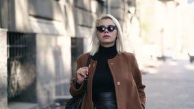 Портрет молодой привлекательной белокурой женщины в городе осени Девушка имеет стильный взгляд, солнечные очки и прошивку носа Да видеоматериал
