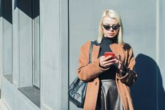 Портрет молодой привлекательной белокурой женщины используя мобильное устройство в городе осени Девушка имеет стильный взгляд, со стоковые изображения rf