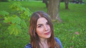 Портрет молодой привлекательной девушки с красивой улыбкой модель смотрит камеру и усмехаться девушка в ярком лете видеоматериал