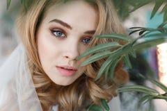 Портрет молодой привлекательной девушки с совершенной кожей среди зеленых листьев Портрет конца-вверх горизонтальный Стоковая Фотография