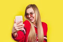 Портрет молодой привлекательной женщины в солнечных очках делая фото selfie на smartphone изолированном на желтой предпосылке Стоковые Изображения