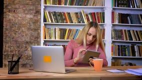 Портрет молодой привлекательной кавказской девушки с прошивкой внимательно работая с планшетом на предпосылке книжных полка видеоматериал