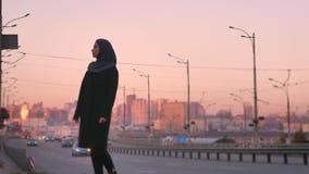Портрет молодой привлекательной мусульманской женщины в hijab готовя проходя автомобили и смотря камеру с городским городом акции видеоматериалы