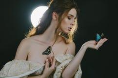 Портрет молодой рыжеволосой женщины в винтажном платье золы с открытым назад и плеч в лунном свете на черной предпосылке S стоковая фотография rf