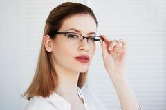 Портрет молодой стильной бизнес-леди в белой рубашке и стеклах стоковые изображения
